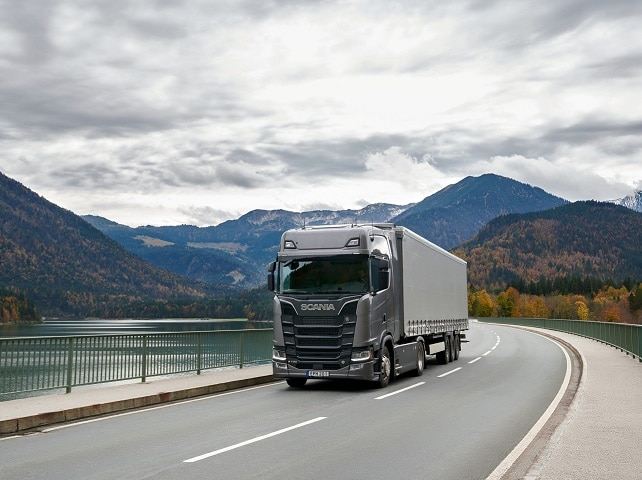 Scania S 730 4x2 beside river and hills
